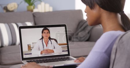 African American woman video chatting with doctor