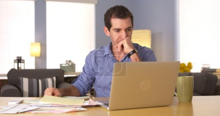 Young man paying bills at home