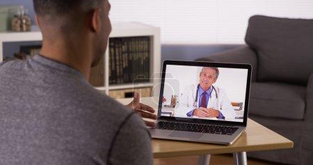 Photo pour Patient noir discutant de problèmes de santé avec un médecin en ligne - image libre de droit