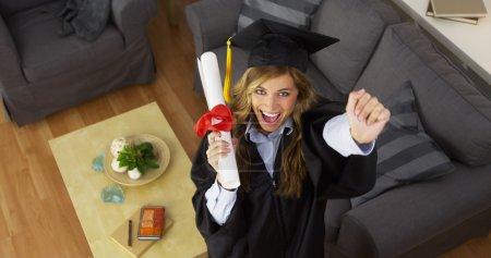 Female graduate celebrating with diploma