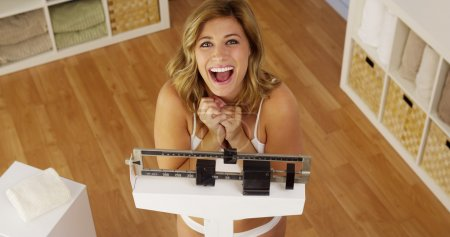Healthy young woman weighing herself on scale