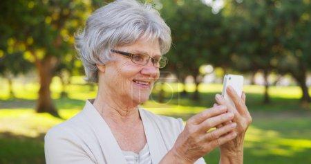 Hip grandma taking selfies at the park