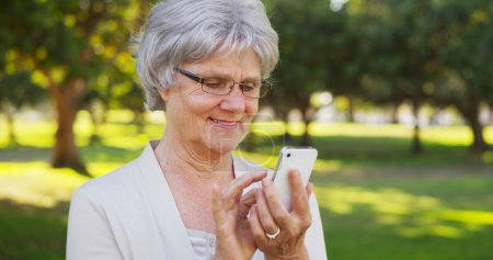 Senior woman texting on smartphone at the park