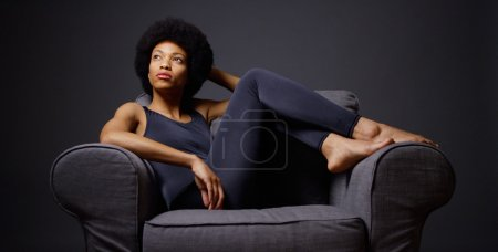 Photo for Black woman sitting in chair thinking - Royalty Free Image
