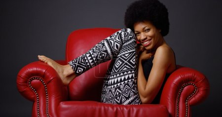 African woman sitting in red armchair