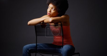 African woman sitting casually with arms over back of chair