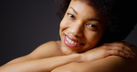 Black woman sitting with arms crossed smiling on grey background
