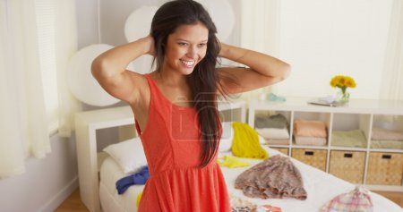 Young Hispanic woman trying on clothes in bedroom