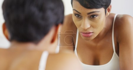 Black woman splashing face with water and looking in mirror