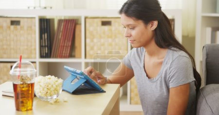 Mixed race woman using tablet on coffee table