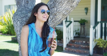 Mixed race woman standing by tree drinking iced tea