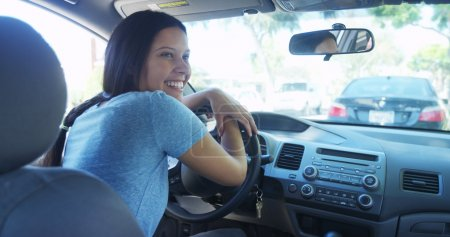 Happy mixed race woman sitting in car waiting