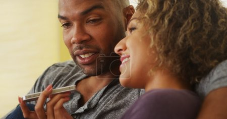 African couple talking on smartphone