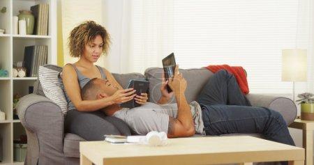 Photo pour Couple de noirs à l'aide de leurs tablettes sur canapé - image libre de droit