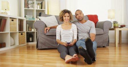 Cute black couple sitting on floor in living room