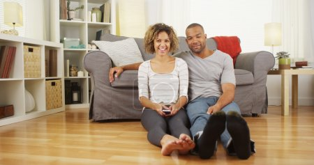 Cute African couple sitting on floor in living room