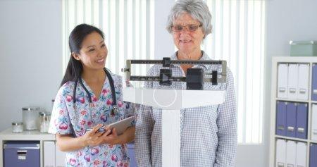 Photo pour Infirmière chinoise pesant patient âgé - image libre de droit