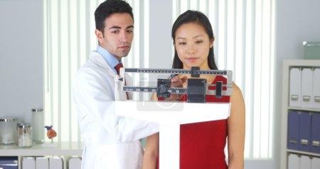 Photo pour Heureux patient chinois pesé sur des balances - image libre de droit