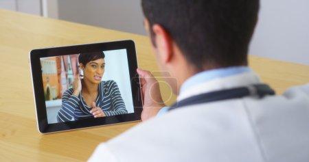 Foto de Médico hispano hablando con el paciente joven en tableta - Imagen libre de derechos