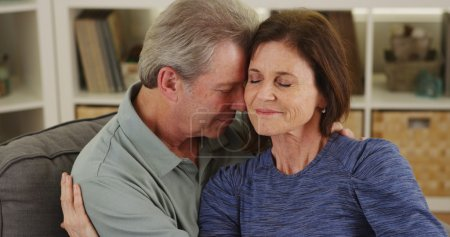 Photo for Loving senior couple cuddling on couch - Royalty Free Image