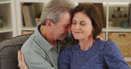Photo pour Aimer le couple de personnes âgées câlins sur le canapé - image libre de droit