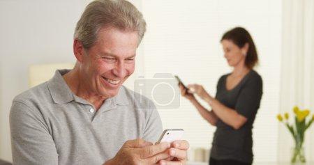 Cheerful senior man using smartphone