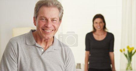 Photo pour Heureux couple de personnes âgées debout dans le salon regardant la caméra - image libre de droit