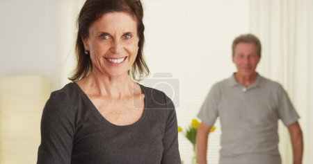 Photo pour Couple âgé debout dans le salon souriant - image libre de droit