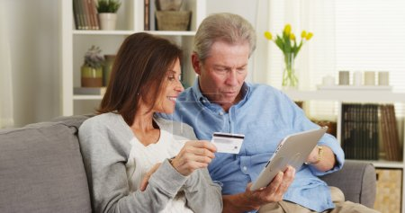 Excited senior couple making a purchase on tablet