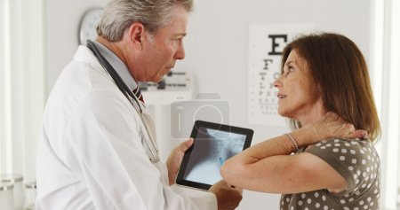 Patient explaining neck problems to senior doctor