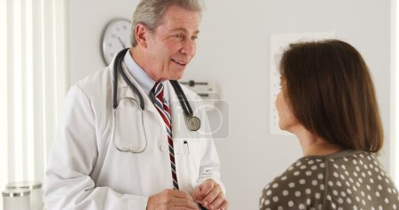 Friendly doctor having a conversation with senior patient