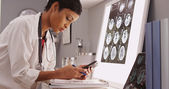 Young attractive doctor texting results of brain scans