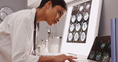 Young female medical assistant looking at x-ray scans
