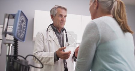 Mid-aged doctor talking to female patient