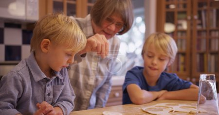 Two adorable white children making cookies with grandma