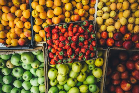 Photo for Ripe juicy fruits and berries are in cardboard boxes summer day on the market. top view - Royalty Free Image