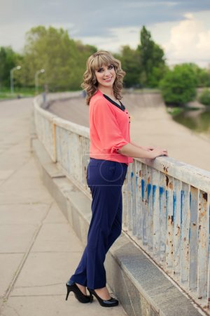 Young woman staying near the bridge . Attractive girl in blouse, pants and heels in the park. Outdoor portrait