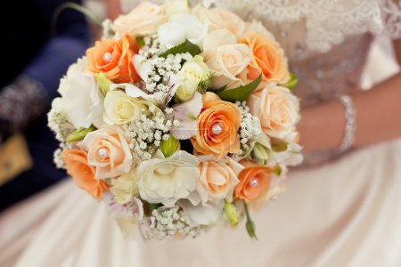 Pastel wedding bouquet with orange roses in hands