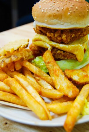 Traditional american burger, freshly french fries with omelette egg