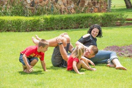 Photo pour Une famille jouant et ayant l'amusement dehors sur la pelouse de leur maison. - image libre de droit