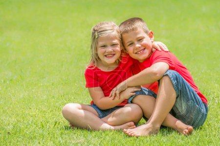 Photo pour Deux enfants qui sont frère et soeur sont assis sur la pelouse verte avec des t-shirts rouges et des shorts de jean bleu avec de grands sourires regardant le spectateur à donner l'un l'autre un grand câlin, un beau jour d'été. - image libre de droit