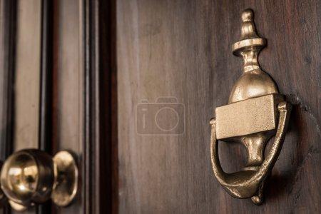 A copper door knocker on a dark brown door....