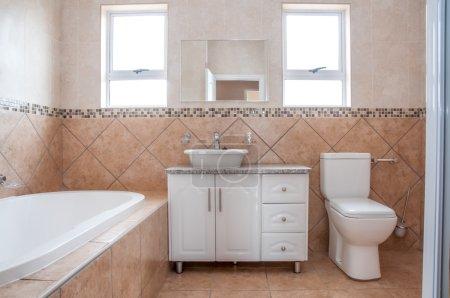 Photo pour La salle de bain neuve d'un nouvellement construire maison, révélant la baignoire, lavabo et les toilettes, tout en blanc, en face de tuiles brunes sur le mur. - image libre de droit