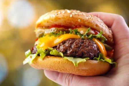 Hand holding warm homemade hamburger outdoors...