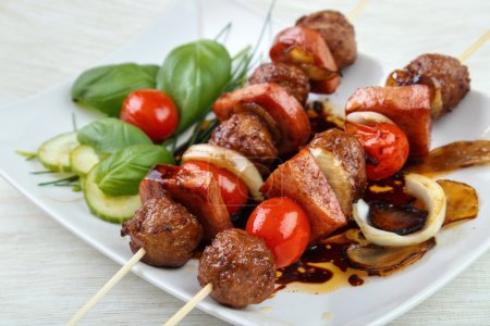 Photo for Grilled meatball skewers with basil leaves and cherry tomatoes on dish - Royalty Free Image