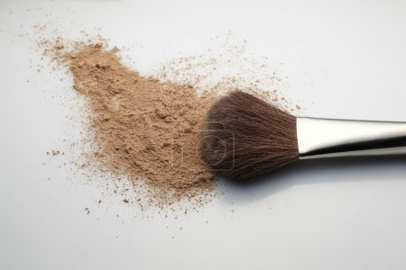 Makeup Brush with beige loose Face Powder placed horizontal on white gradient background