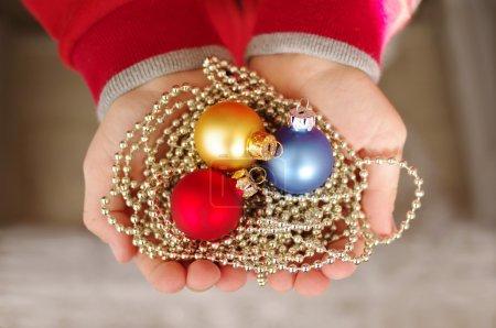 Foto de Tres bolas de Navidad de varios colores brillantes en las manos del niño - Imagen libre de derechos