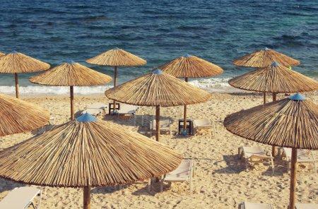 Bambusovými slunečníky proti moři.