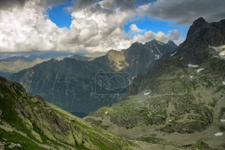 Two lakes hidden high in mountain in between rocky peaks under tragic cloudy sky