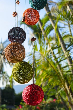 Stylish thread colorful handmade balls in front of green palm tree bokeh